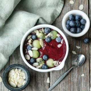 Smoothieskål med skogsbær, kiwi og mandler