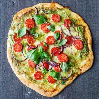 Pizza med ruccalopesto og tomater